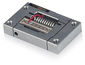 Figure 10. Low-cost piezo flexure amplified actuators for OEM application. The image shows the integrated piezo stack actuator and the preload. A position feedback sensor is optional (Image: PI)