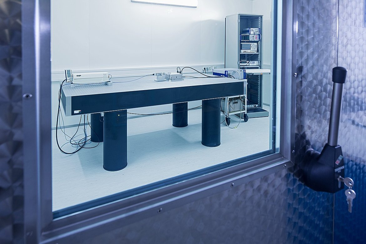 View inside PI's 6-fold isolated nano-metrology lab. The vault-like door keeps acoustic vibration out. NOTE: all electronics are off the vibration isolated table. The table with its isolators rests on a concrete slab separated from the foundation of the building. The lab is situated in the basement, for minimum structural vibration, and is designed as a room inside a room, again on a separate foundation. Inside the lab, a water-cooled ceiling is used to remove air turbulence and vibrations from air conditioning fans. The cabinet, with the measuring electronics, is enclosed and equipped with a heat exhaust system. This setup is crucial for nanometer and sub-nanometer precise measurements. (Image: PI)