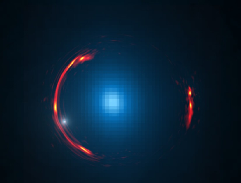 Composite image of the gravitational lens SDP.81 showing the distorted image of the more distant galaxy (red arcs) and the nearby lensing galaxy (blue center object). By analyzing the distortions in the ring, astronomers have determined that a dark dwarf galaxy (data indicated by white dot near left lower arc segment) is lurking nearly 4 billion light-years away. (Image: Y. Hezaveh, Stanford Univ.; ALMA (NRAO/ESO/NAOJ); NASA/ESA Hubble Space Telescope))